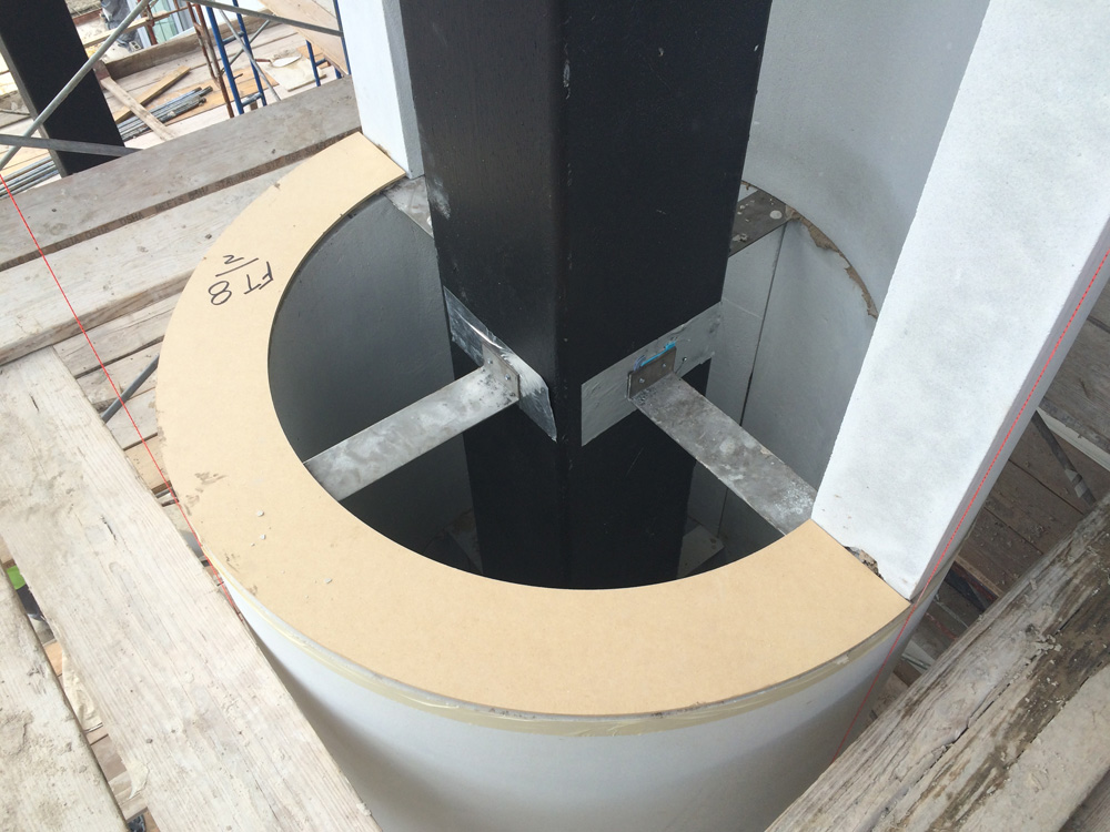 Cast stone pieces for column secured using steel plates and anchors